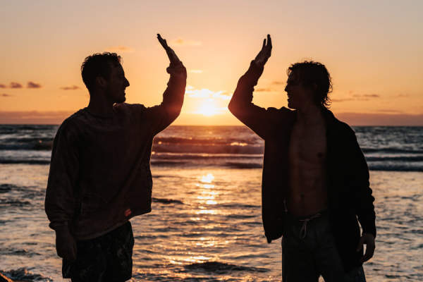 silhouette of two men high-fiving