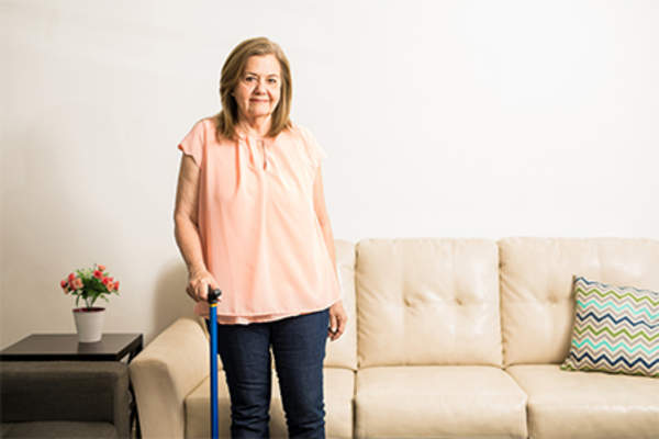 Woman using walking cane in living room at home.
