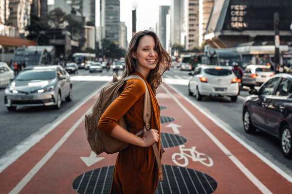 woman smiling wearing backpack in city