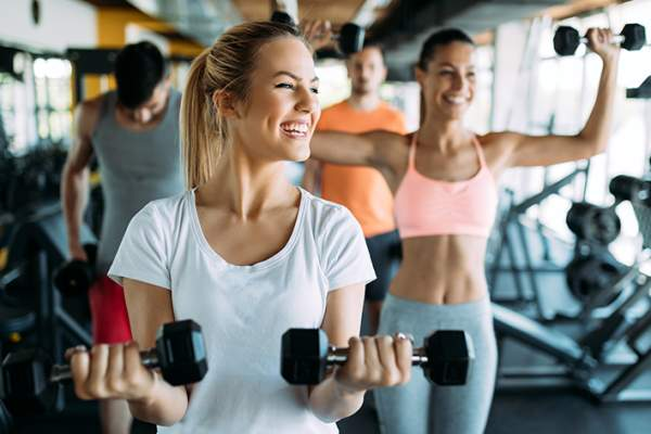 Smiling young women exercising at gym.