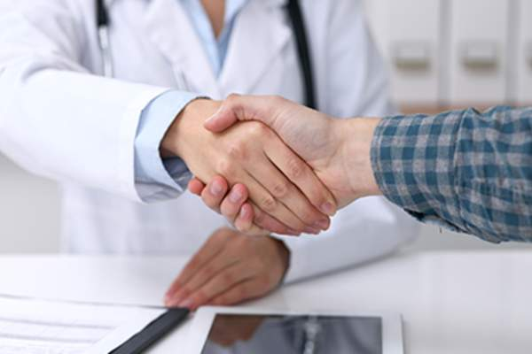 Patient shaking hands with a doctor.