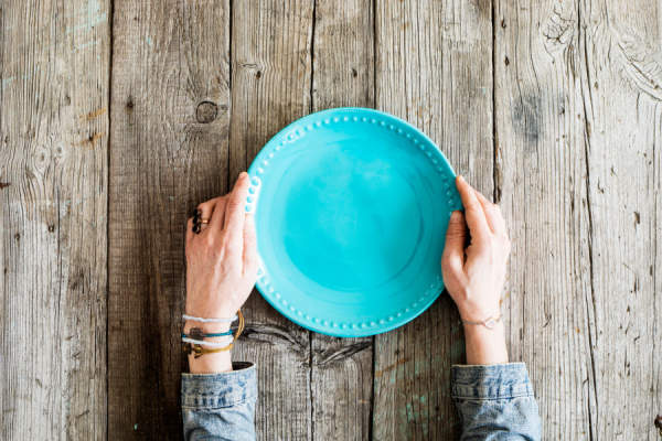 Woman hands holding blank plate on wooden table
