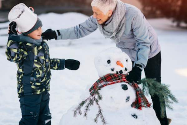 Grandmother playing with grandchild in snow.