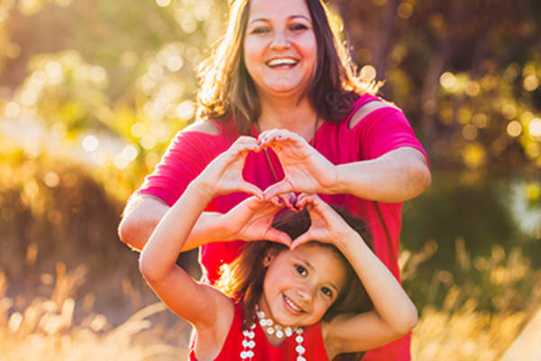 Woman and young girl smiling and making heart symbols with hands.