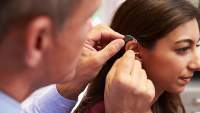 Doctor fits a patient for a hearing aid.