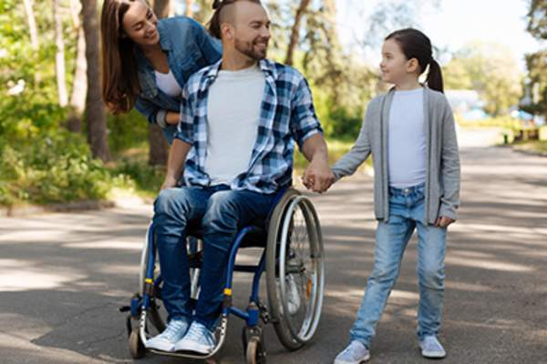 Man in a wheelchair outside with his family.