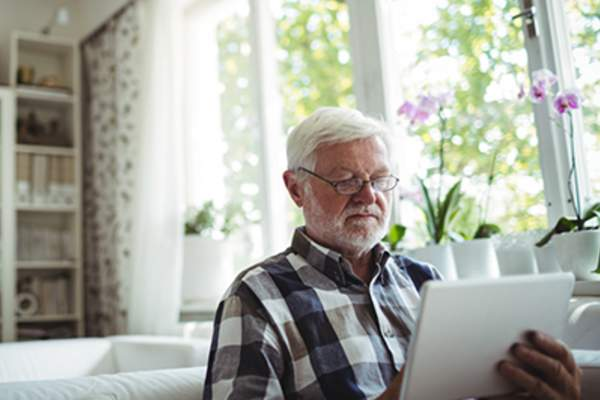 Elderly man on tablet at home near window.