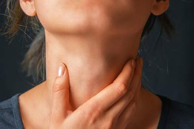 Woman holding her throat image.