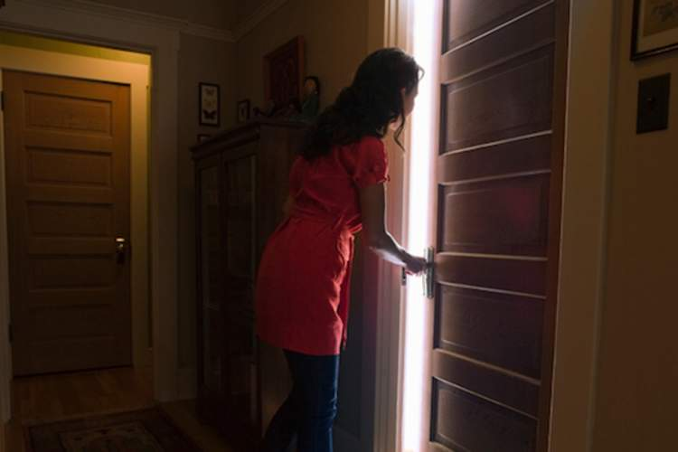Woman opening door to bedroom.