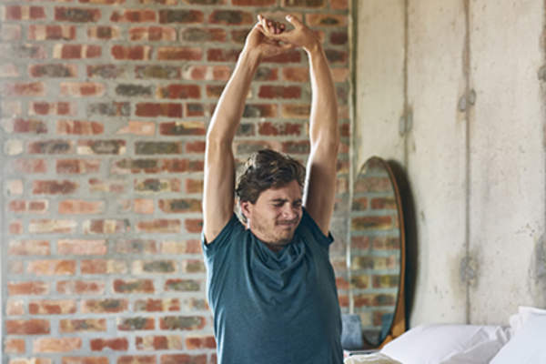 Man stretching arms sitting on bed.