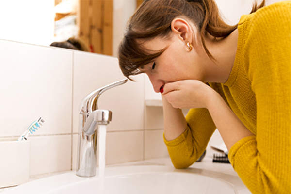 Woman with nausea from ulcerative colitis leans over the sink holding her mouth.
