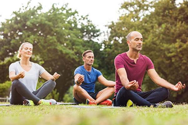 Group of people meditating in a park.