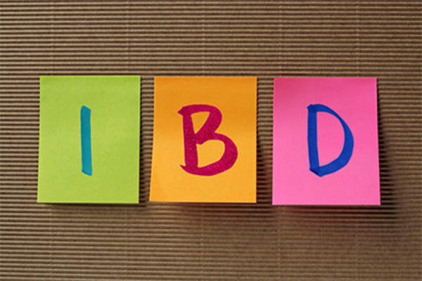 Letters IBD on colorful sticky notes on board.
