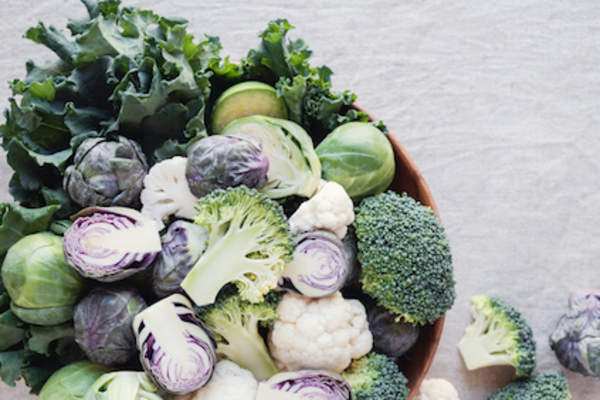 Cruciferous vegetables, cauliflower,  broccoli, brussels sprouts, and kale in wooden bowl