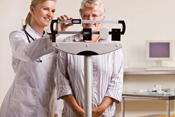 Senior woman being weighed by her doctor.
