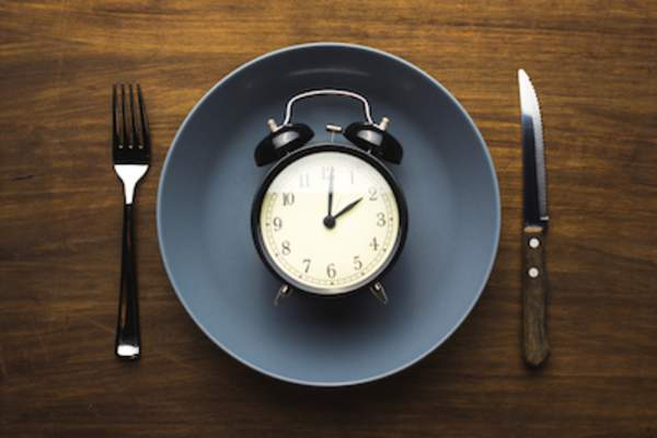 Time to eat concept, a clock on plate.