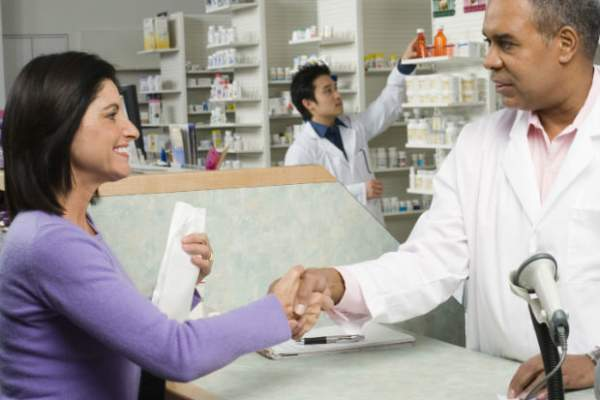 Smiling woman shaking pharmacist's hand.