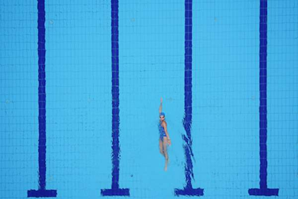 Overhead view of woman swimming laps in pool.