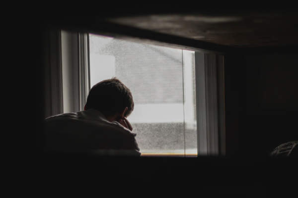 depressed man near window