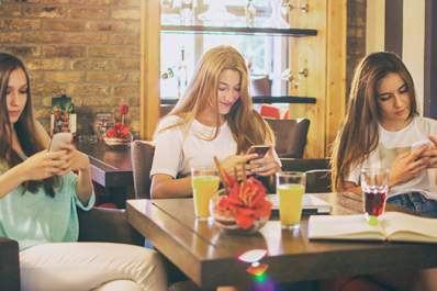 Teen girls on cell phones at cafe.