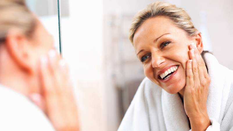 Middle age woman admiring her skin in the mirror.