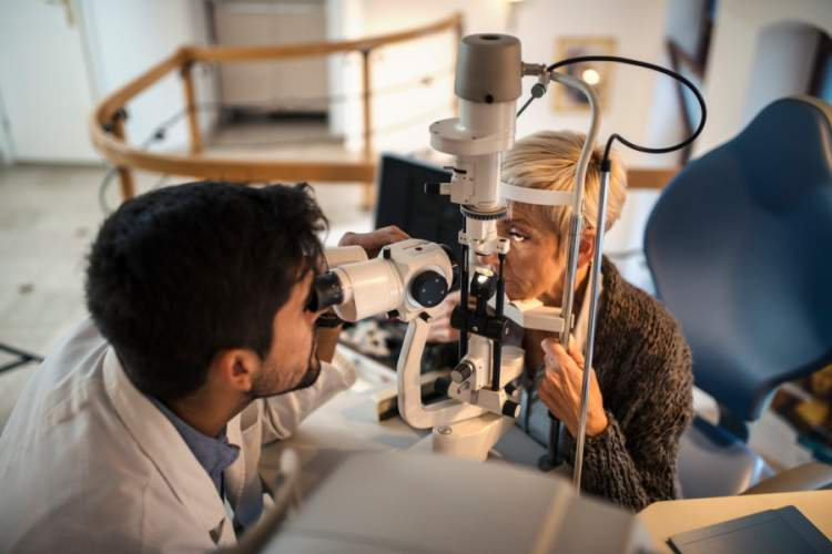 Young ophthalmologist checking eyesight of senior woman