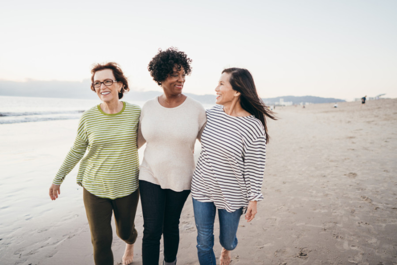 three senior women walking on beach together