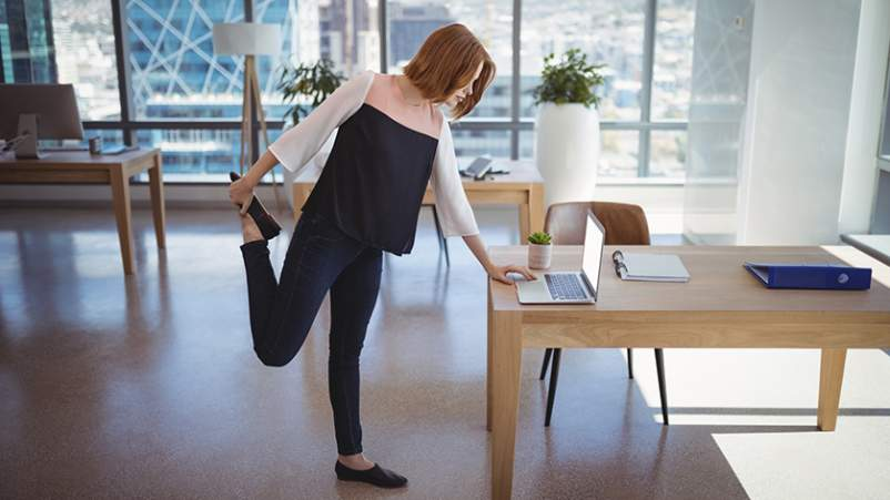 Woman doing stretches at her office desk.