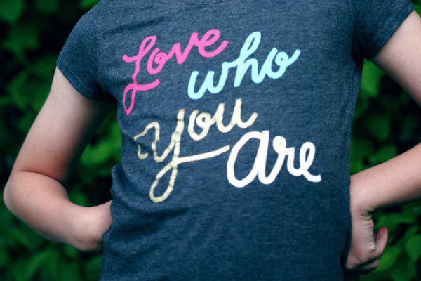 "girl wearing shirt that reads ""love who you are"""