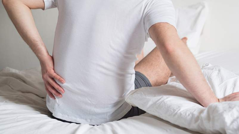 Man with sciatica sitting up on bed.