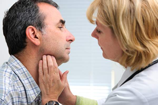 Doctor checking man's lymph nodes.