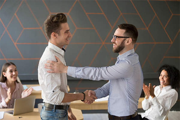 Boss congratulating man at work for good job done.