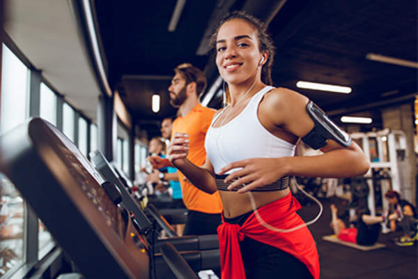 Young woman running on treadmill.