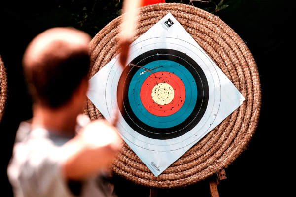 man shooting a target with an arrow