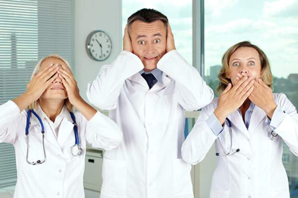 Three doctors with hands over mouth, eyes, ears.