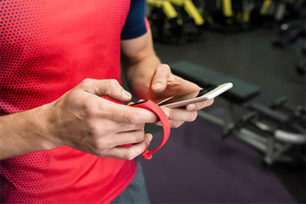 Man using fitness tracker and smartphone app.