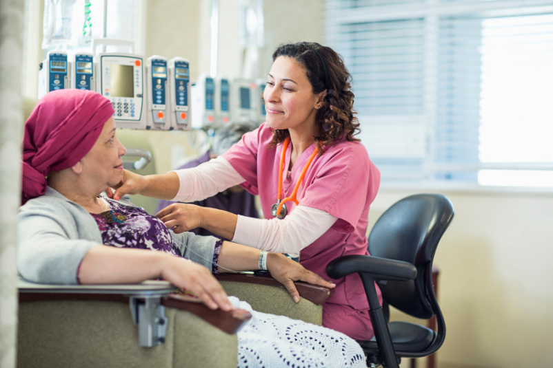 senior latina woman in headscarf getting chemo treatment talking to nurse