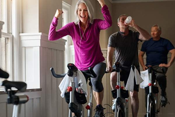 Woman cheering on an exercise bike.