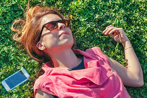 Woman lying in the grass next to her cell phone.