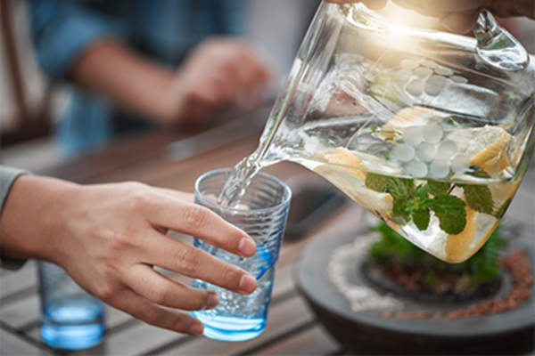 Pouring a glass of water with lemon and mint.