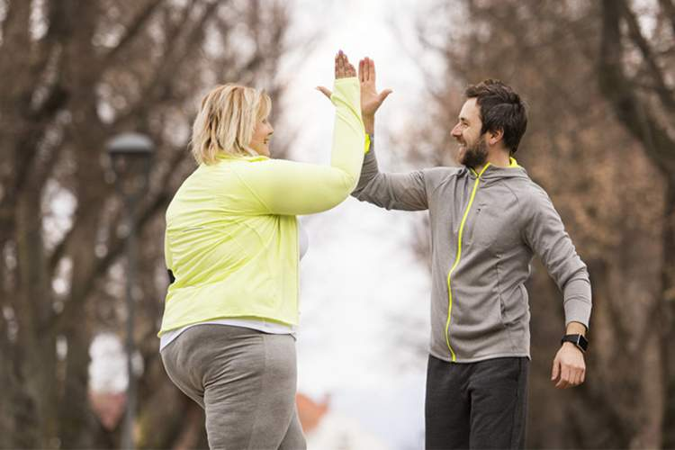Trainer high fives an overweight woman exercising in the park.