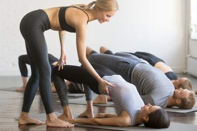 Yoga instructor helping people in yoga class do bridge pose on mats.