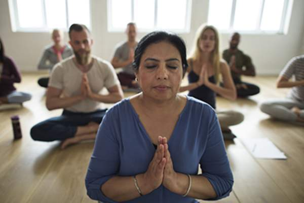 People meditating in yoga class.