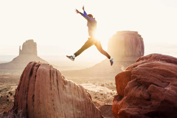 man jumping over rocks in Monument Valley