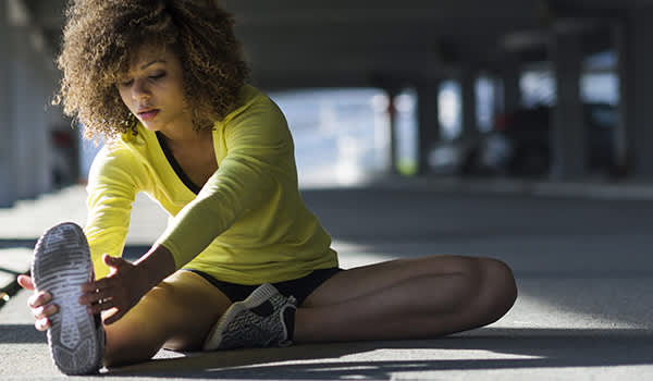 Girl stretching and listening to the music on her headphones