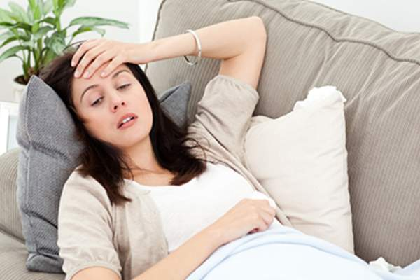 Woman feeling nauseous and lying down on the couch.