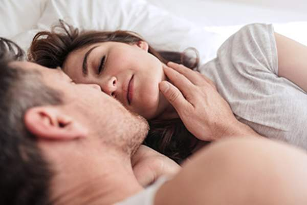 Man touching a woman's face in bed.