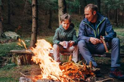Father and son sitting around campfire.