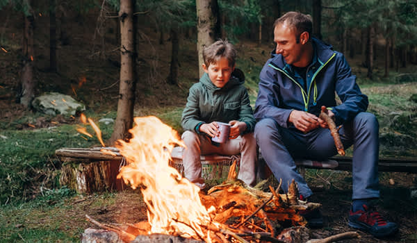 Father and son around campfire.