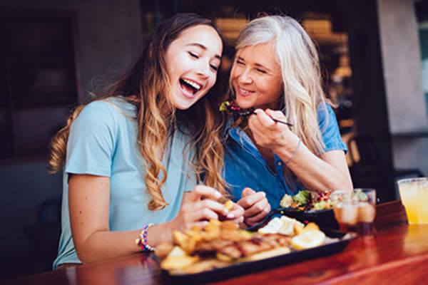 Women eating and laughing together.
